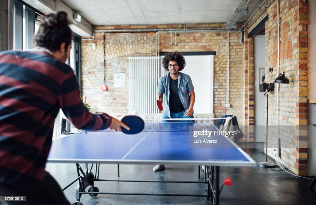 Businessman playing table tennis with colleague : Stock Photo