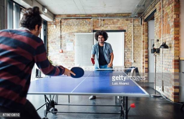 businessman playing table tennis with colleague - table tennis stock pictures, royalty-free photos & images