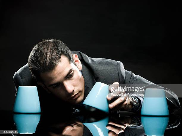 businessman playing the shell game - shell game stock photos and pictures