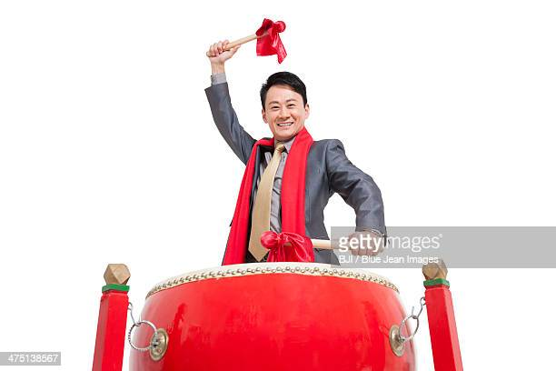 Businessman playing traditional Chinese red drum