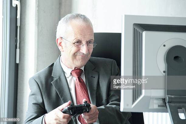 businessman playing video games at desk - sigrid gombert stock pictures, royalty-free photos & images