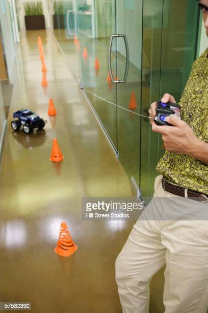 businessman playing with an rc car in the hallway - remote controlled stock photos and pictures