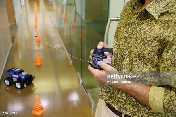 businessman playing with an rc car in the hallway - rc car stock photos and pictures