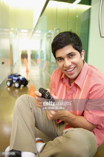 Businessman playing with an RC car in the hallway