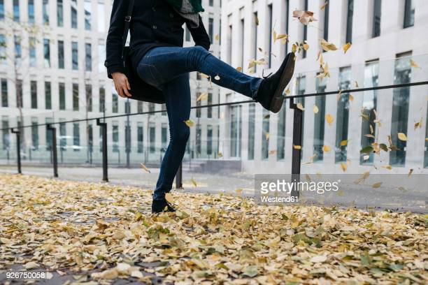 Businessman playing with autumn leaves in the city, partial view