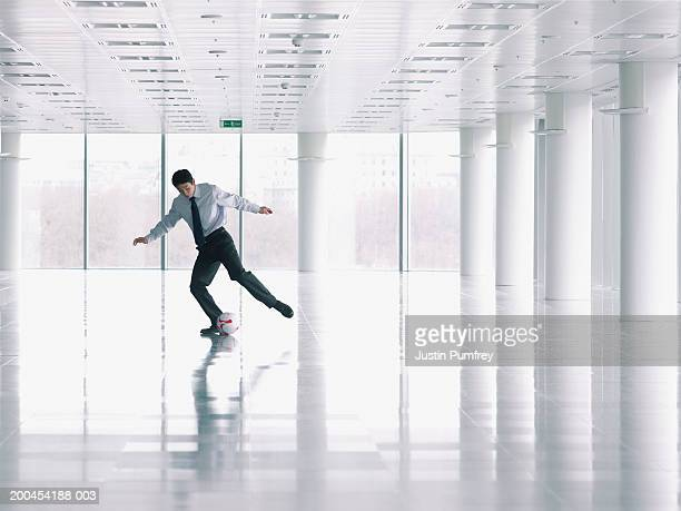 Businessman playing with football in empty office space