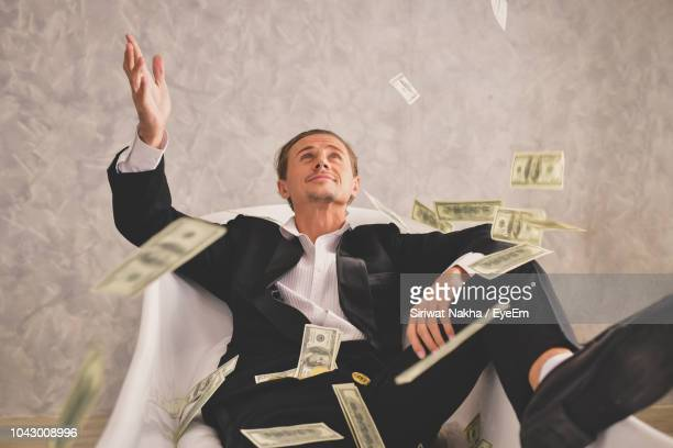 businessman playing with paper currency while sitting on chair in office - ricchezza foto e immagini stock