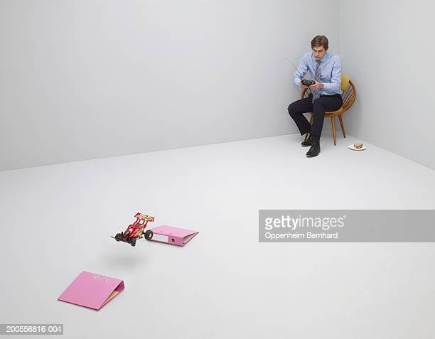 businessman playing with remote control car in room - remote control car games stock photos and pictures