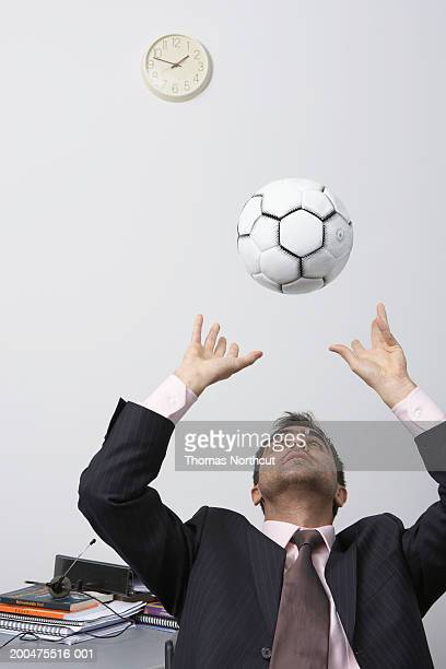 Businessman playing with soccer ball at desk, looking up