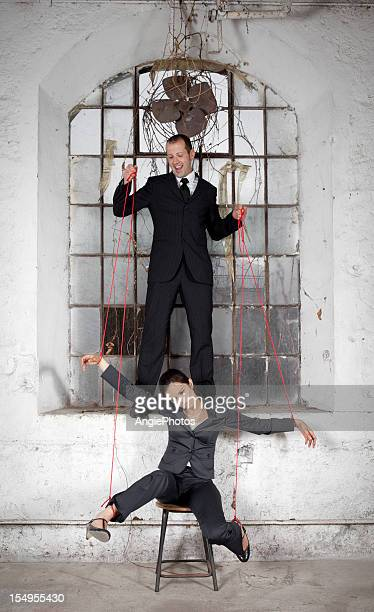Businessman playing with woman like a marionette