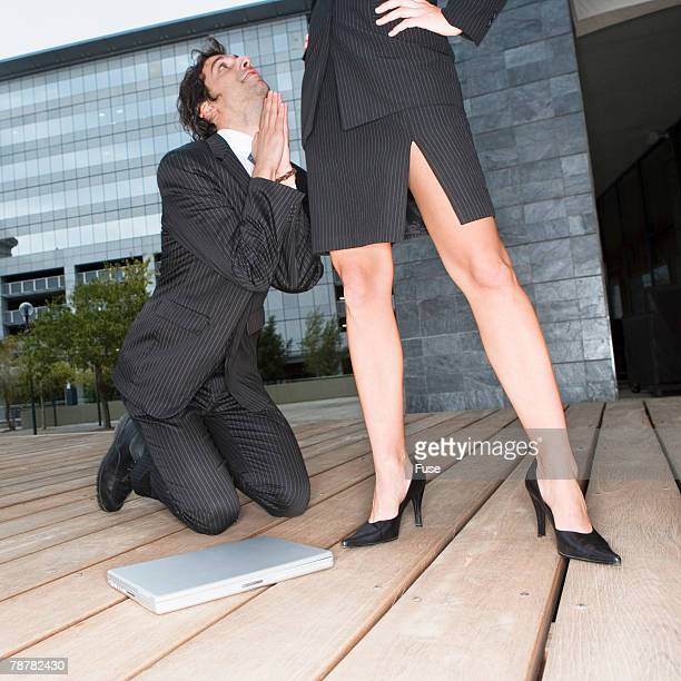 businessman pleading with businesswoman - women dominating men stock photos and pictures