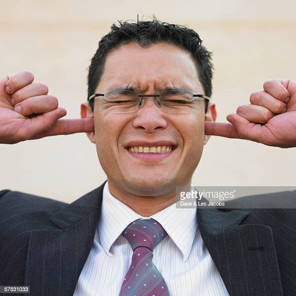 Businessman plugging his ears