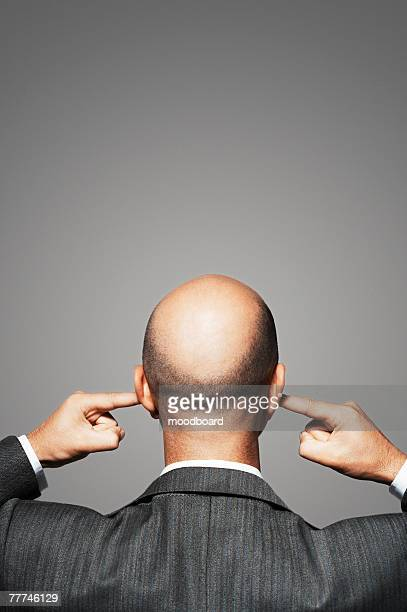 businessman plugging his ears - fingers in ears stock pictures, royalty-free photos & images