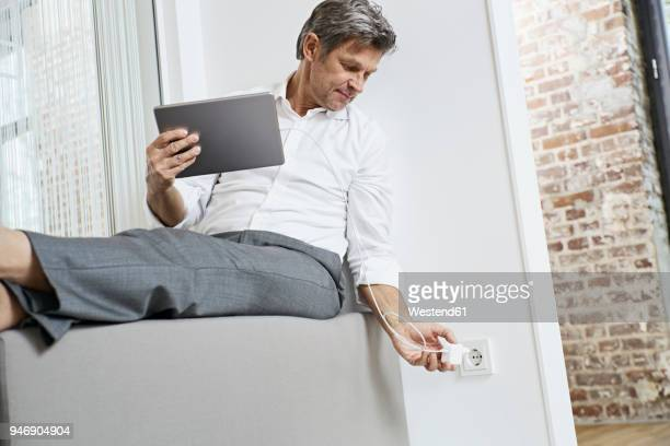 Businessman plugging in tablet