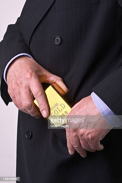 Businessman pockets gold bar