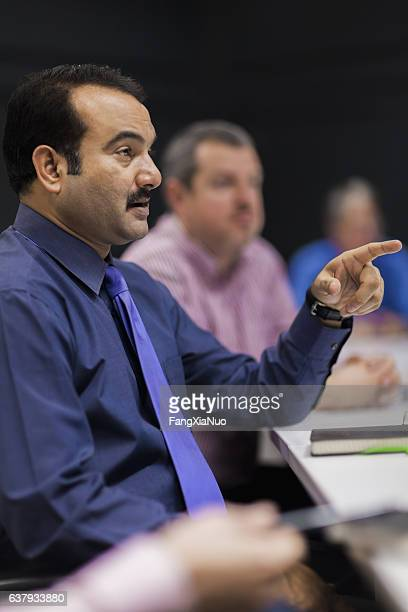 businessman pointing across table in meeting - plaintiff stock pictures, royalty-free photos & images