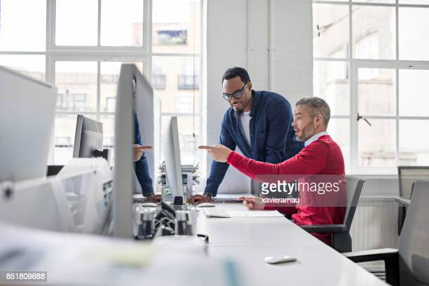 Businessman pointing at computer to colleague
