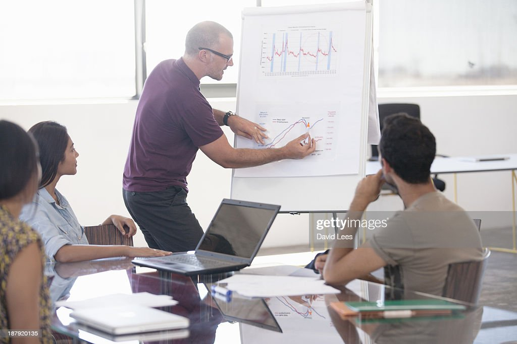 Businessman pointing at flip chart in meeting : Stock Photo