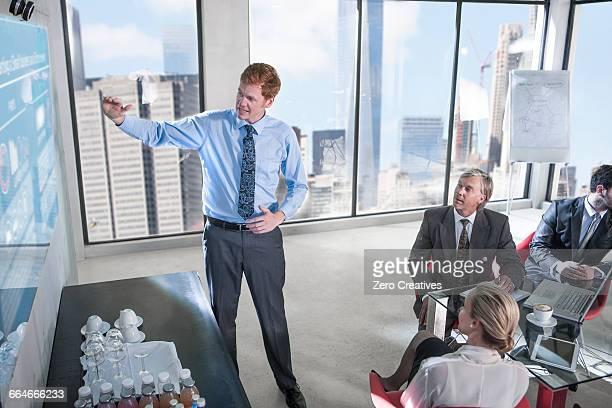 Businessman pointing at screen at presentation, New York, USA