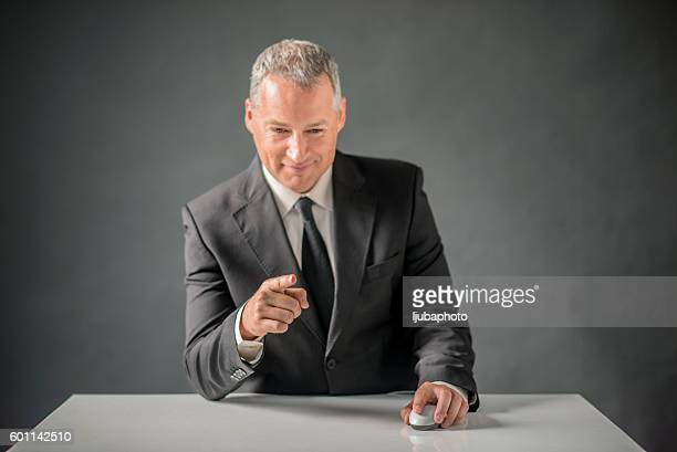 Businessman pointing at something and holding computer mouse ove