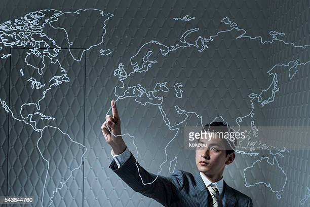 Businessman pointing at the map of the world in company