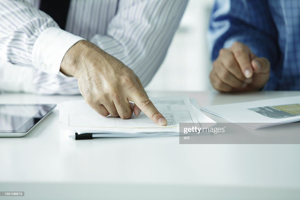 Businessman pointing finger at plans : Stock Photo
