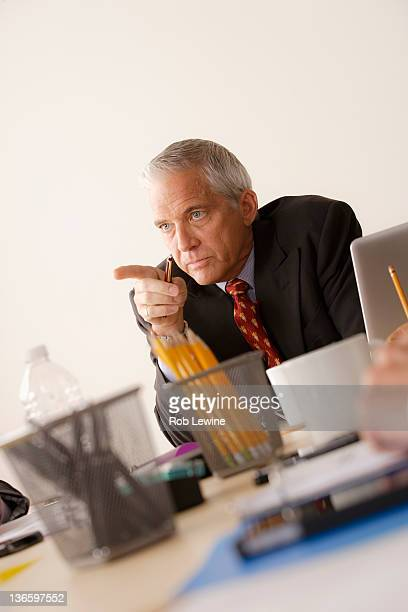 Businessman pointing finger from behind desk