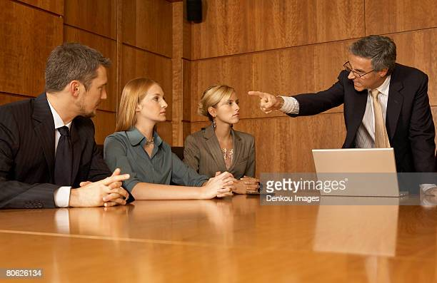 Businessman pointing his finger to his three colleagues in a board room