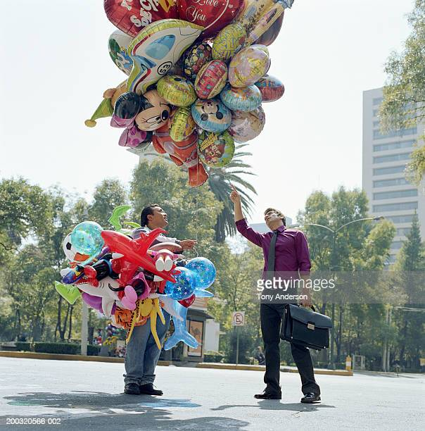 Businessman pointing to balloon held by vendor