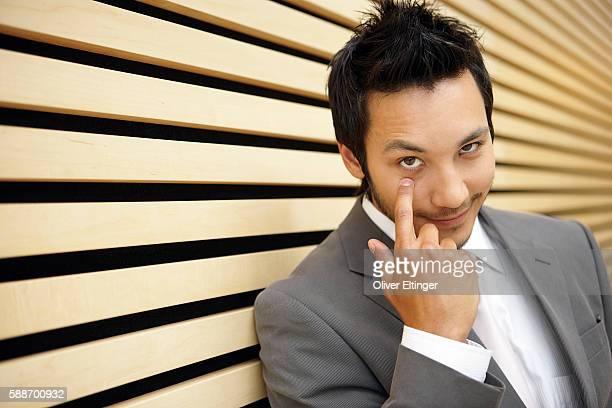 businessman pointing to his eye - oliver eltinger stock-fotos und bilder