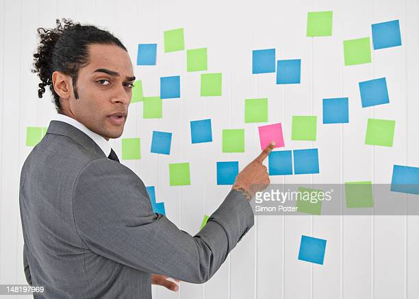 businessman pointing to sticky note - turning stock pictures, royalty-free photos & images