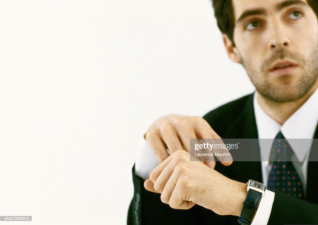 Businessman pointing to watch and looking up : Stockfoto