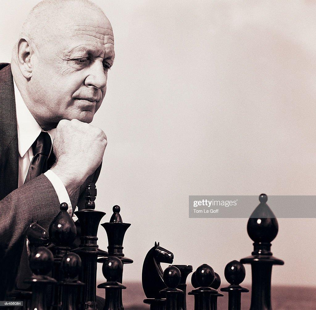 Businessman pondering chess move : Stock-Foto