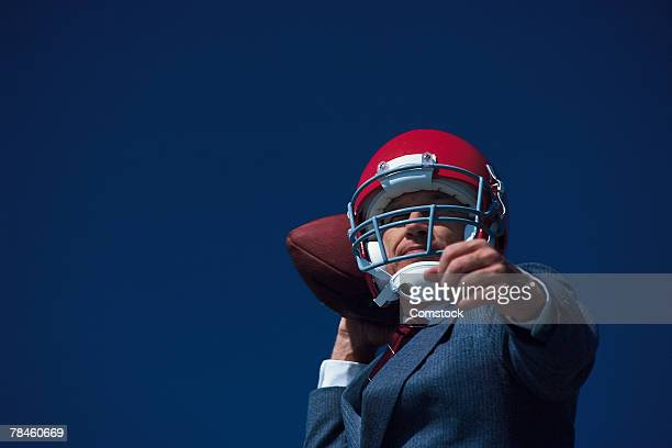 businessman posing in football helmet with ball - quarterback stock pictures, royalty-free photos & images
