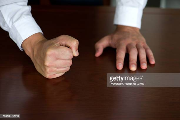 Businessman pounding fist on table, cropped