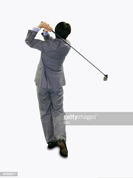 businessman practicing golf swing in office, rear view - golf swing stock pictures, royalty-free photos & images