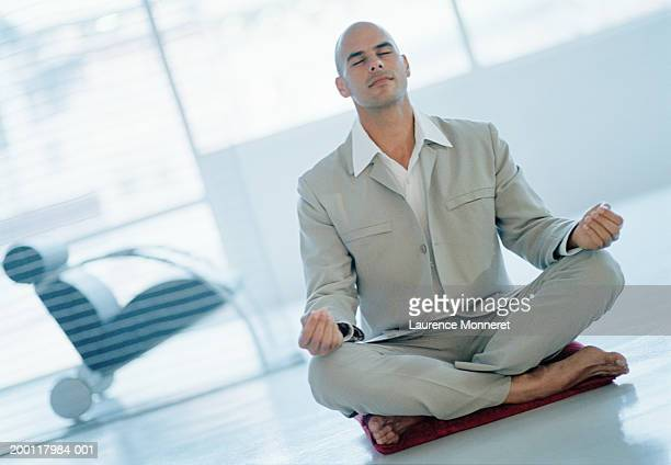 Businessman practicing lotus position, eyes closed