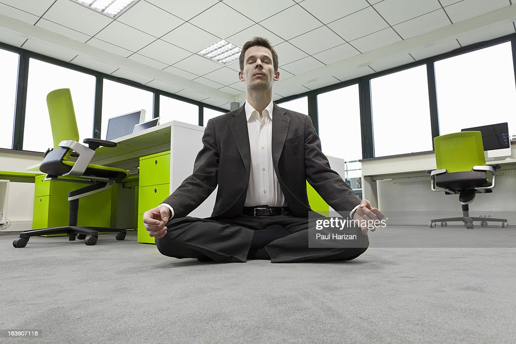 businessman practicing meditation in office : Stock Photo