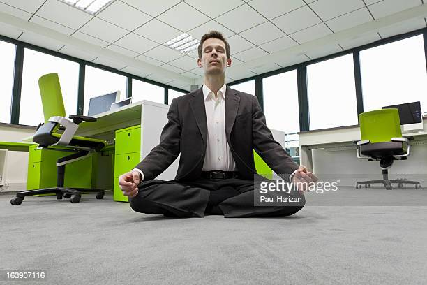 businessman practicing meditation in office