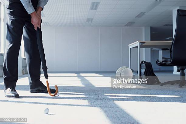 Businessman practicing putting with umbrella, in office, low section