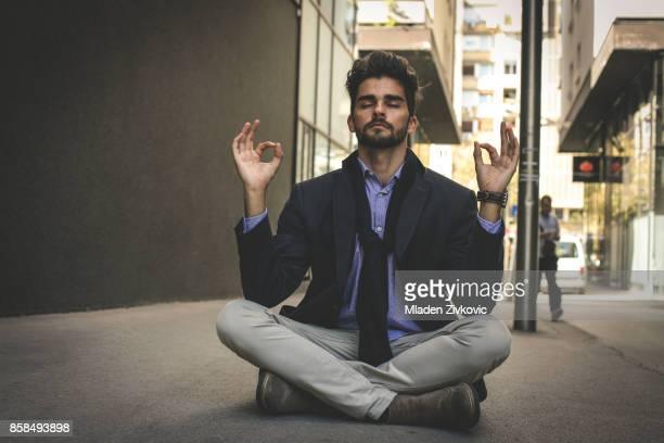 Businessman practicing yoga on the street.