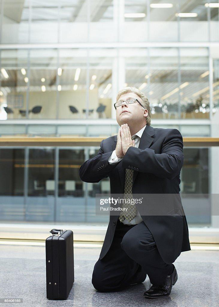 Businessman praying in building lobby : Stock Photo