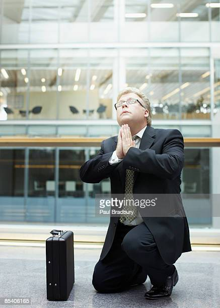 Businessman praying in building lobby