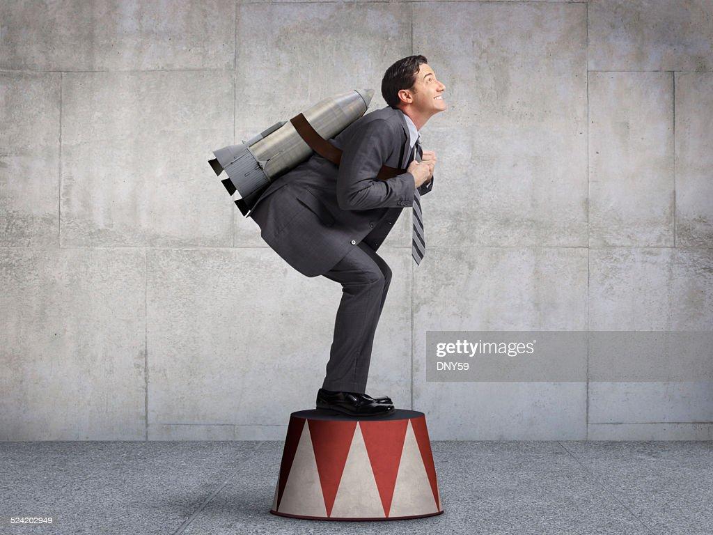 Businessman Preparing For Takeoff On Circus Pedestal : Stock Photo