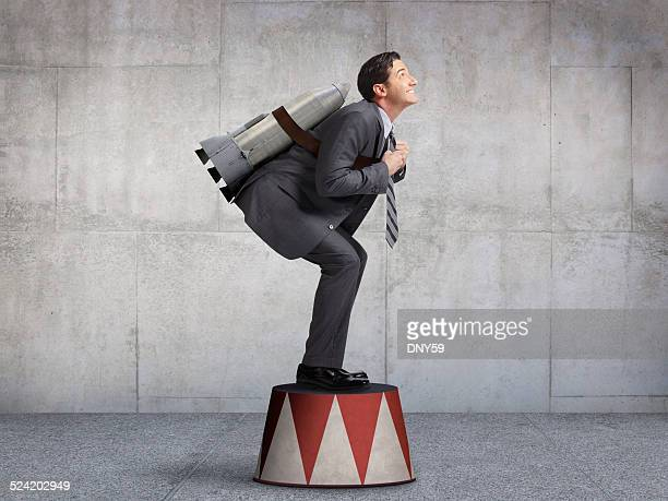 businessman preparing for takeoff on circus pedestal - circus stock pictures, royalty-free photos & images