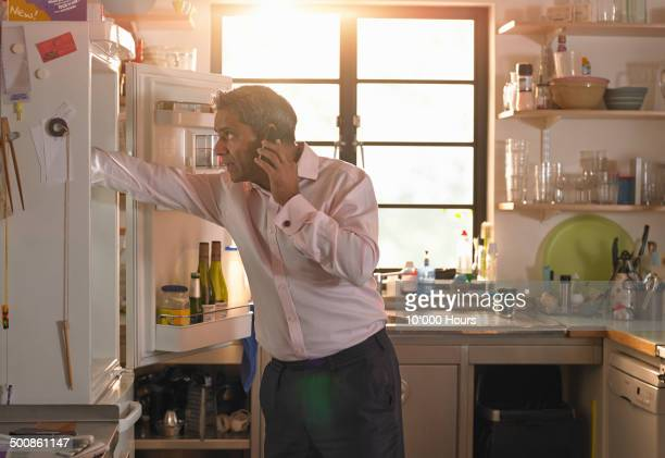 businessman preparing meal and talking on phone - white goods stock pictures, royalty-free photos & images