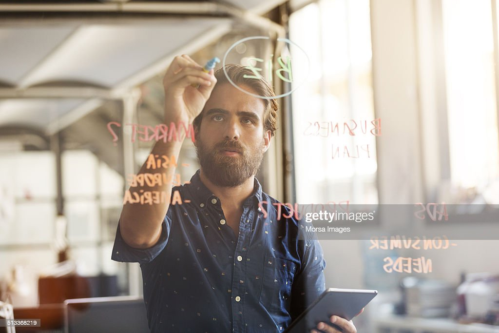Businessman preparing plan on glass wall : Stock Photo