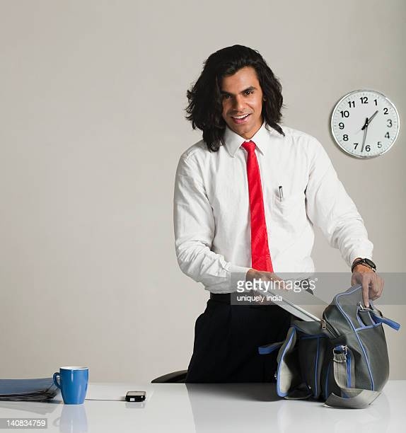businessman preparing to leave the office - putting stock photos and pictures