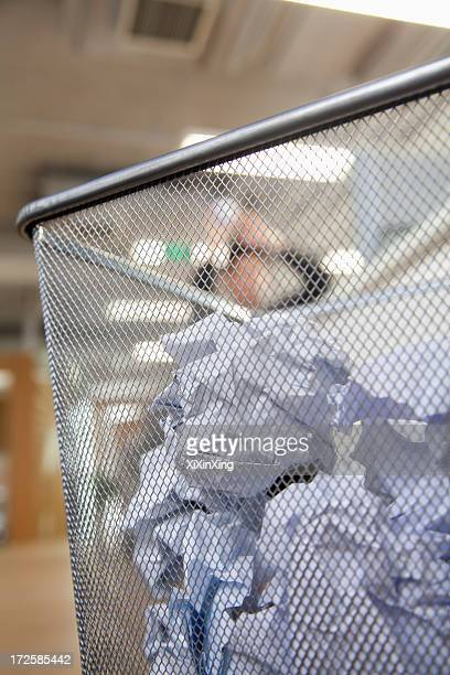 Businessman preparing to throw paper into wastepaper bin, close up on wastepaper bin