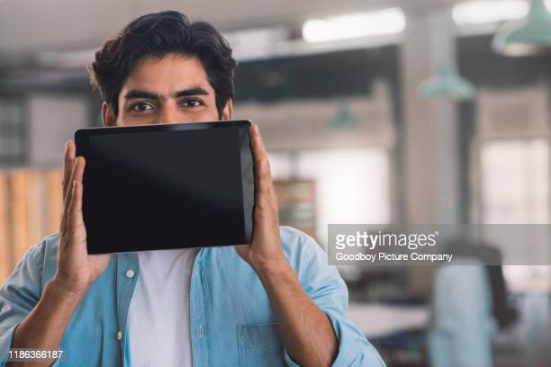 businessman presenting a digital tablet with a blank display - obscured face stock pictures, royalty-free photos & images